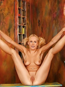 Curly-haired blonde with pigtails posing naked next to a bike