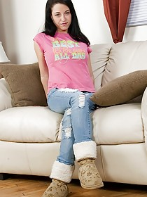Euro trash get-up brunette shows off her smooth pussy on a couch