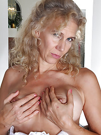 Curly-haired blonde MILF fingering her dripping pussy on a couch