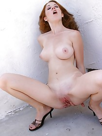 Redhead takes off her pink bra and colorful panties outdoors