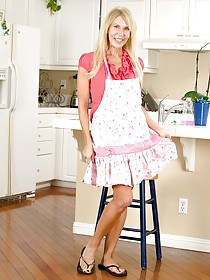 Apron-wearing blonde MILF with a really long face shows her pussy