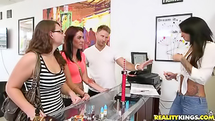 Horny brunette and sweet blonde with glasses are enjoying wild threesome with busty partner in the public shop. They are taking care of his big dick.